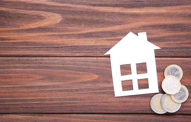Дом из белой бумаги с монетами на коричневом фоне