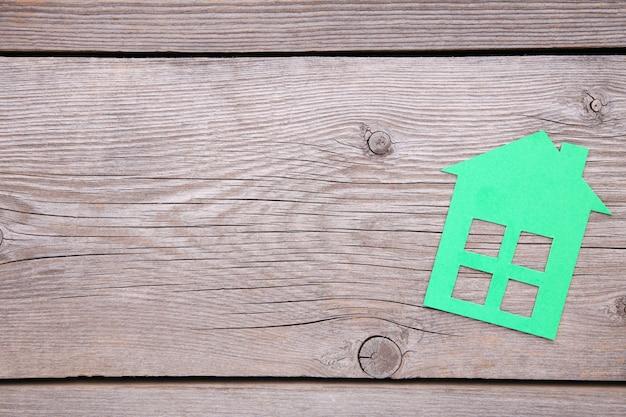 灰色の木製の背景に緑の紙の家