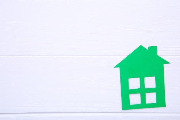 白い背景の上の緑の紙の家
