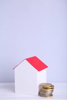 Дом из белой бумаги с красной крышей, с монетами на сером фоне