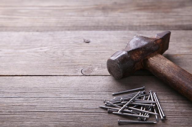 古いハンマーと灰色の背景テーブルの上の爪のイメージ