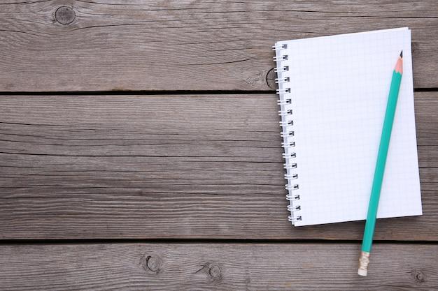 メモ帳と木製のテーブルの上の鉛筆