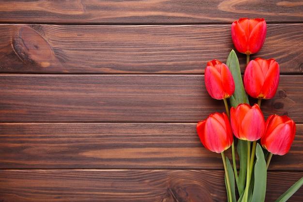 茶色の木製の背景に赤いチューリップ