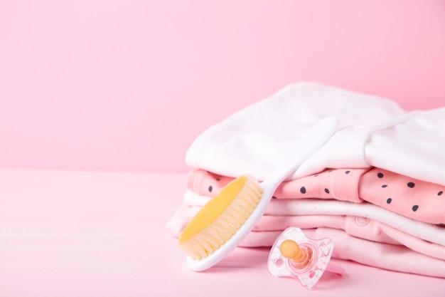 Детская одежда с расческой на розовом с копией пространства