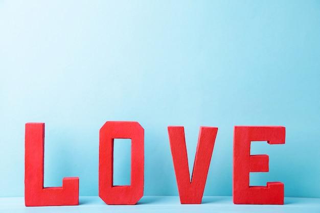 Красные буквы любят на синем. любовь слово.