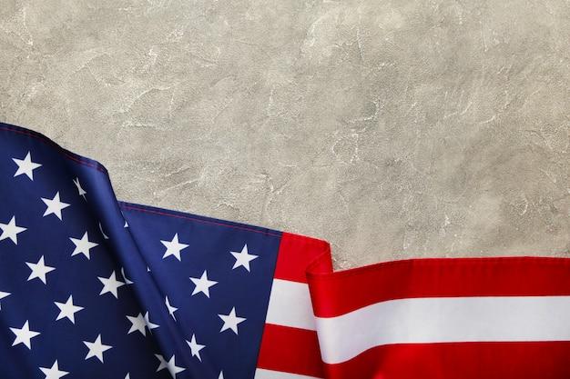 コピースペースを持つ灰色のコンクリート背景にアメリカの国旗