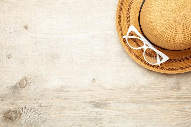 Винтаж изготовить соломенной шляпе и солнцезащитные очки на светлом фоне.
