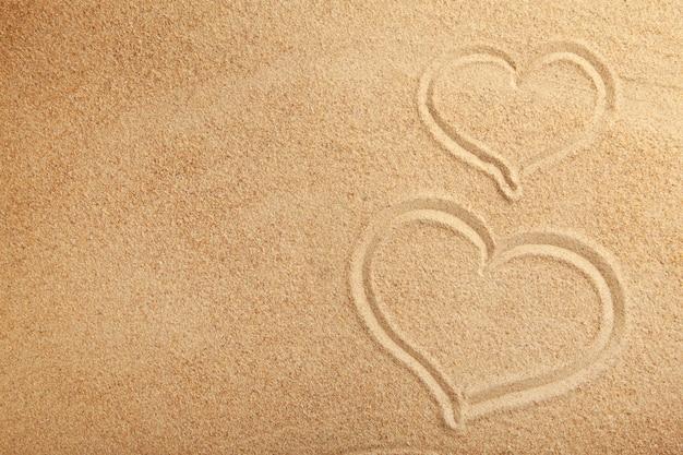 Рисование сердца на песке. летняя концепция