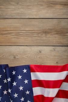 コピースペースを持つ灰色の木製の背景にアメリカの国旗