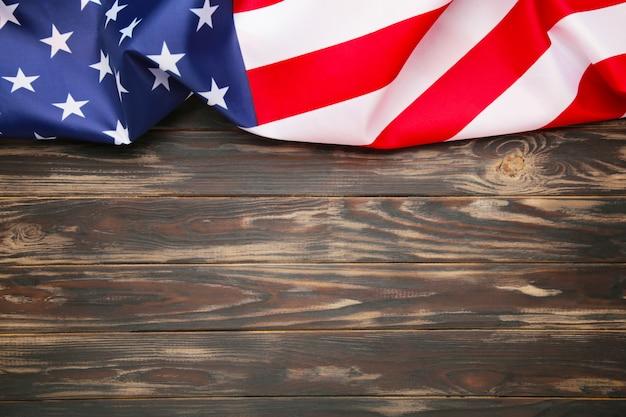 コピースペースを持つ茶色の木製の背景にアメリカの国旗