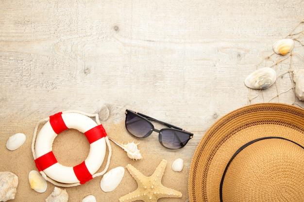 Пляжная шляпа с ракушками и песком на светлом фоне