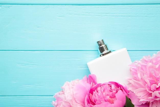 青色の背景にピンクの花と香水の白いボトル