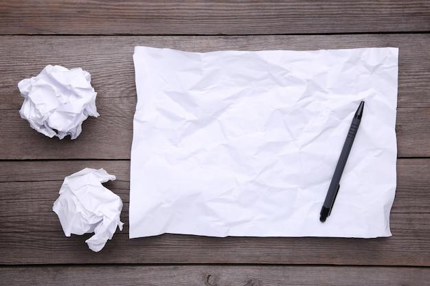 Стек белой бумаги с ручкой на серый деревянный