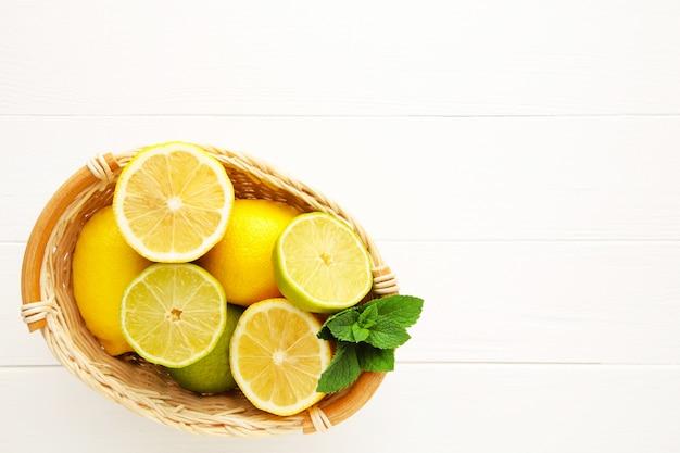 Органические лимоны и лаймы в корзине на белой деревянной стене с копией пространства