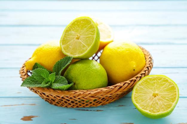 Органические лимоны и лаймы в корзине на синей деревянной стене