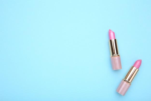 青い背景にピンクの口紅、フラットを置く