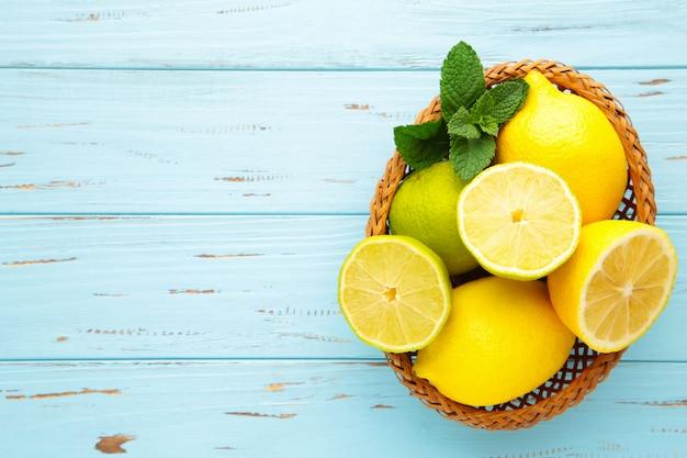 Органические лимоны и лаймы в корзине на синей деревянной стене с копией пространства