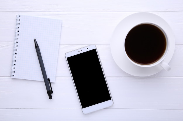 ノートブックと白い木製の背景にコーヒーのカップを持つスマートフォン