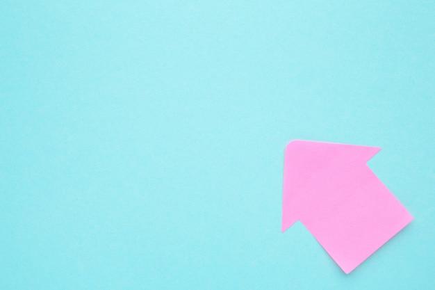 Розовая бумага стрелка формы на синем фоне для творческих проектов. вид сверху