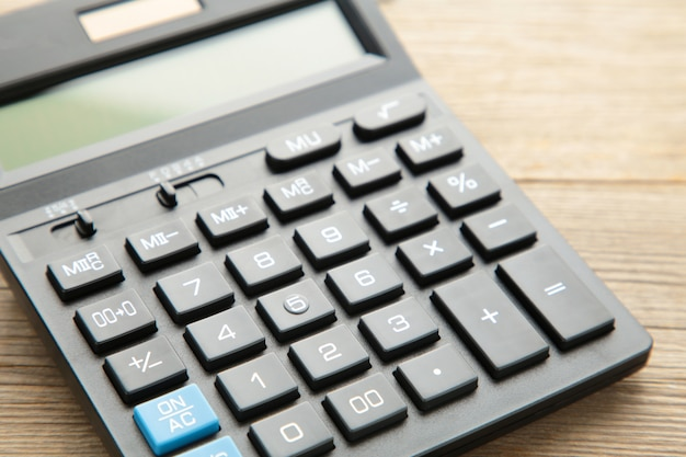 Калькулятор на сером фоне деревянных, макро фото