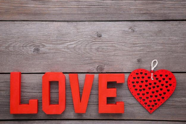 赤い文字の愛と灰色の背景に心。愛という言葉。