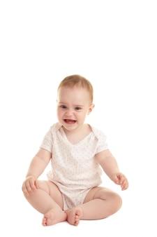 Грустная девочка сидит и плачет на белом фоне
