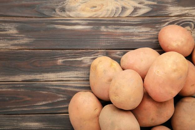 コピースペース、トップビューで茶色の背景にジャガイモ。