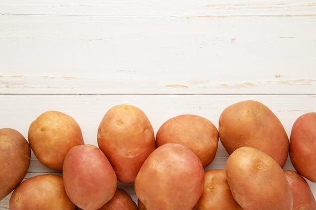 白い木製の背景、上面にジャガイモ