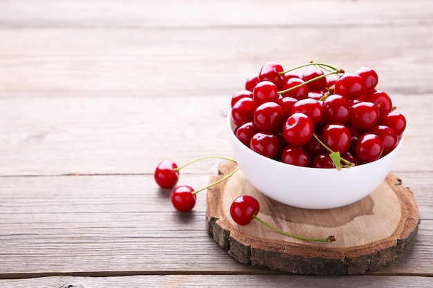灰色の木製テーブルの上の皿に新鮮な赤いチェリーフルーツ