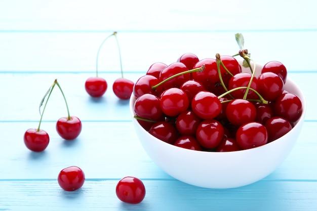 青い木製のテーブルの上皿に新鮮な赤いチェリーフルーツ