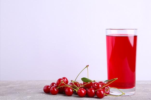 Стакан вишневого сока и ягод на сером с копией пространства
