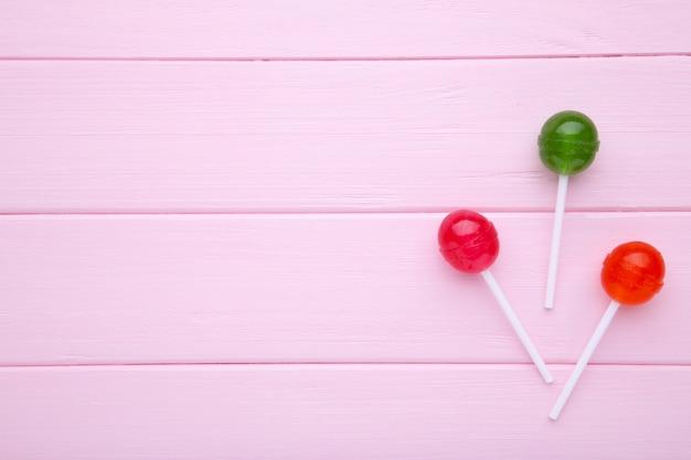 ピンクの背景のロリポップ。甘いキャンディ。