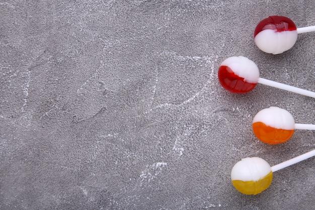 灰色のコンクリート背景にロリポップ。甘いキャンディ。