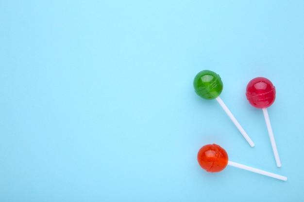 青色の背景にロリポップ。甘いキャンディ。