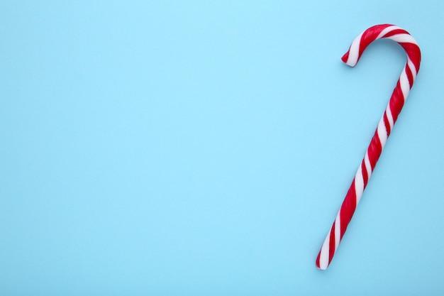 青色の背景、お菓子に赤いキャンディー杖