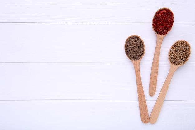 白い木製の背景に木製のスプーンでスパイスをミックスします。上面図
