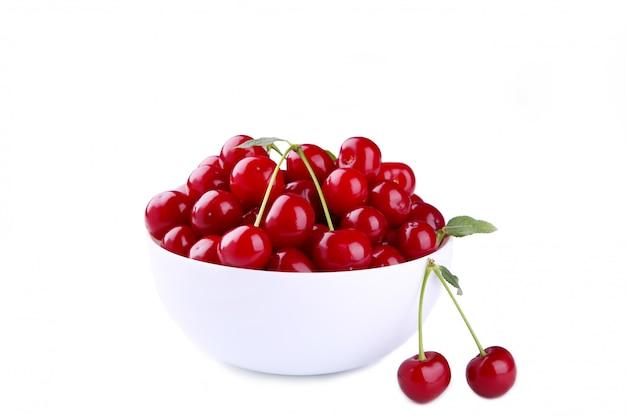 ボウルに白の新鮮な赤いチェリーフルーツ