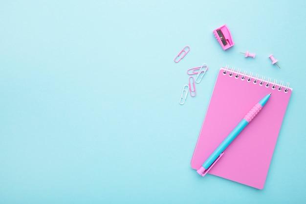 青色の背景にピンクの学校のアクセサリー