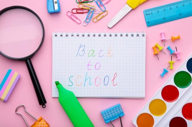 ピンクの背景に学用品と学校に戻る碑文