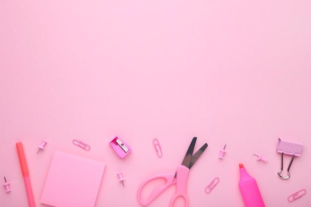 ピンクの背景にピンクの学校のアクセサリー。学校概念、ミニマリズムに戻る