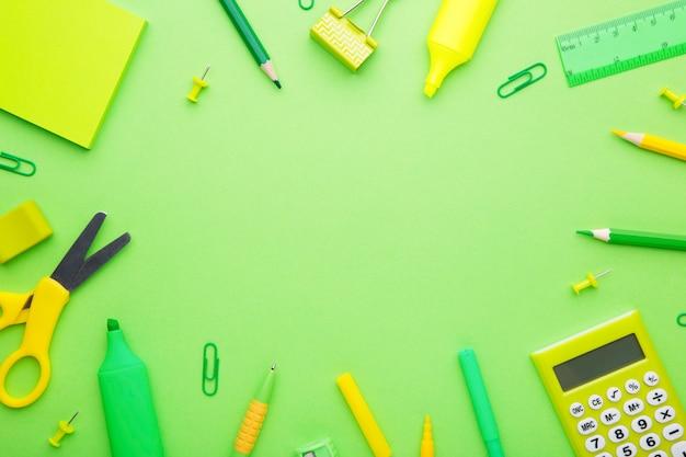 明るい緑の背景に緑の学校のアクセサリー。学校概念、ミニマリズムに戻る