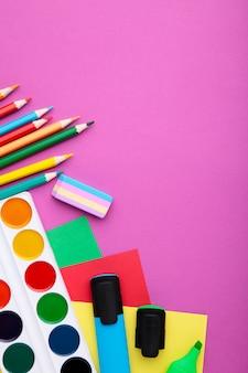 新学期のコンセプト。ピンクの背景、トップビューで学用品
