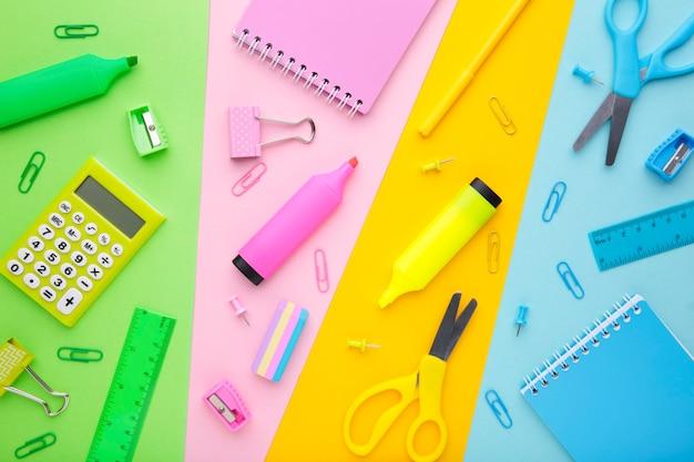 Снова в школу концепции. школьные принадлежности на цветном фоне