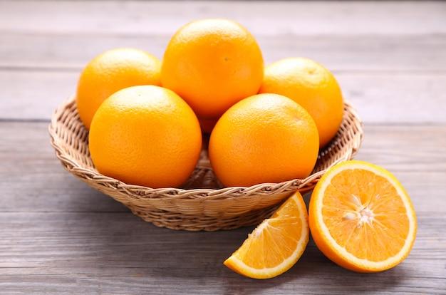 灰色の背景上のバスケットのオレンジ色の果物