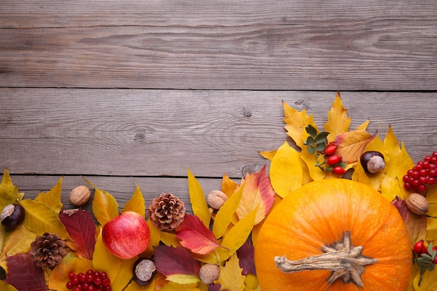 オレンジ色のカボチャの葉と野菜の灰色のテーブル