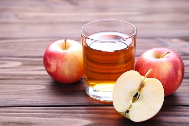 茶色の背景にジュースと赤いリンゴ