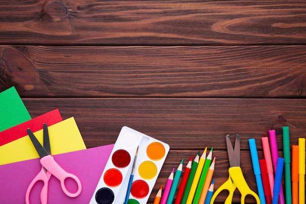 茶色の木製の背景に学校概念に戻る
