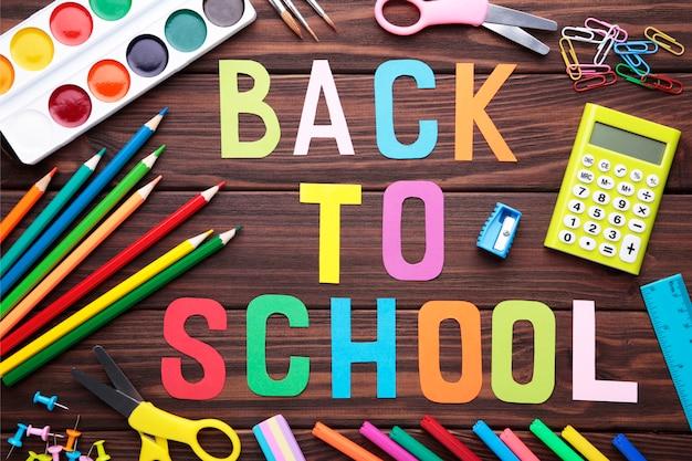 茶色の木製の背景に学用品と学校に戻る碑文