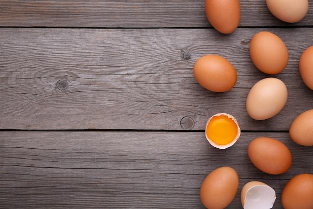 Куриные яйца и половина с желтком на сером фоне.