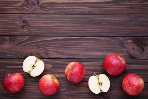 茶色の木製の背景に新鮮な赤いリンゴ